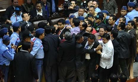 Kerumunan anggota DPR mencoba menghampiri pimpinan sidang saat sidang paripurna di Kompleks Parlemen Senayan, Jakarta, Jumat (26/9)dini hari. Pembahasan RUU Pilkada masih berjalan alot sehingga terjadi hujan interupsi.
