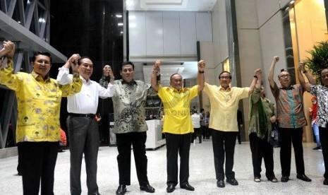 Ketua Umum Partai Golkar Aburizal Bakrie (tengah) bersama jajaran pengurus partai mengangkat tangan bersama usai menggelar konferensi pers terkait penyenggelaraan Munas ke-7 Partai Golkar di Jakarta, Selasa (25/11) malam. (Republika/WIhdan)