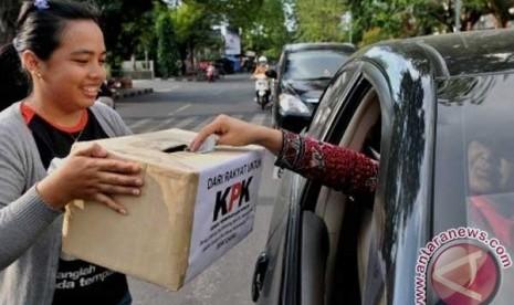Koin Untuk KPK Seorang pengendara mobil memasukan uang ke dalam kotak sumbangan yang dibawa aktivis dari Komite Penyelidikan Pemberantasan Korupsi, Kolusi, dan Nepotisme (KP2KKN), saat berlangsung penggalangan dana