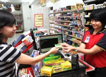 Konsumen membeli token PLN Prabayar di kasir Alfamart.
