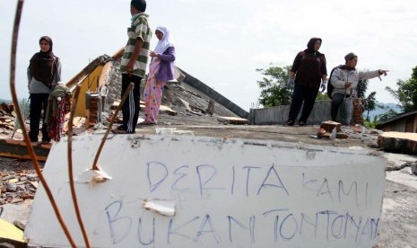 Korban Gempa berdiri diantara puing-puing bangunan rumahnya yang rusak akibat gempa bumi di Desa Blang Mancung Bawah, Ketol, Aceh Tengah, Aceh, Jumat (5/7).    (Antara/Irwansyah Putra)