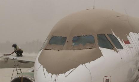 Petugas membersihkan abu vulkanik yang menutupi badan pesawat di Bandara Adi Sutjipto, Yogyakarta, Jumat (14/2). (Antara/Regina Safri)