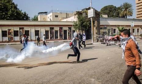 Pendukung Presiden terguling Muhammad Mursi melempar balik tabung gas air mata yang ditembakkan oleh pasukan keamanan di Universitas Kairo, Giza, Mesir, Rabu (26/3).    (AP/Amru Taha)