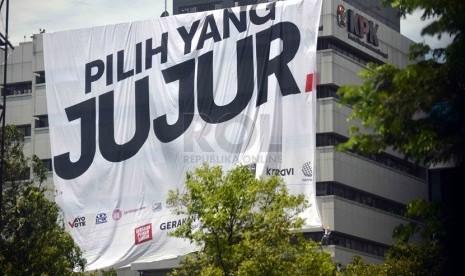 Pemanjat dari Federasi Panjat Tebing Indonesia memasang spanduk raksasa bertuliskan 'Pilih Yang Jujur' di Gedung KPK Jakarta, Selasa (8/4). (Republika/Agung Supriyanto)