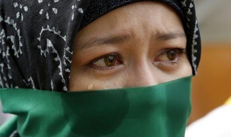 Seorang wanita muslim Filipina menangis saat berunjuk rasa menuju Kedutaan Israel  di Taguig, Metro Manila, Selasa (15/7), mengutuk serangan militer Israel ke wilayah penduduk Gaza . (Reuters / Erik De Castro)