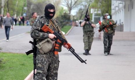 Milisi pro-Rusia bersenjata lengkap berjaga di jalan raya di kota Lugansk, Ukraina, Selasa (29/4).