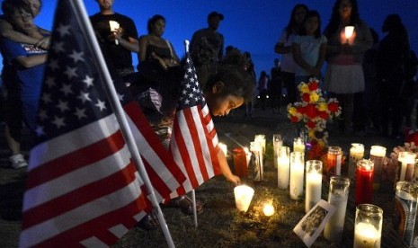 Myia Young (4 years) places a candle by an American flag during a vigil for victims behind a theater where a gunman open fire at moviegoers in Aurora, Colorado July 20, 2012. A total of 71 people were shot in Friday's rampage at the Denver-area movie theat
