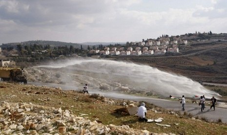 Palestinian and left-wing Israeli demonstrators run away as a foul smelling water cannon is fired by Israeli in the West Bank village of Nabi Saleh, near Ramallah, last year. Conflict of Israel and Palestine become the hottest spot in the world in modern e