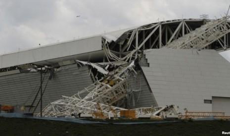 Para pekerja bangunan berdiri di dekat sebuah derek yang rubuh di stadion Sao Paulo Brasil.