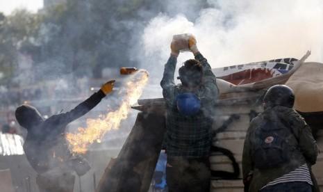 Para pengunjuk rasa melemparkan bom molotov dan kembang api untuk dilemparkan ke arah polisi anti huru hara di Istanbul Taksim Square,Turki, Selasa (11/6).    (Reuters/Murad Sezer)