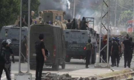 Pasukan militer Mesir melemparkan gas air mata ke arah pendukung Presiden Mursi di Kairo, Rabu (14/8).