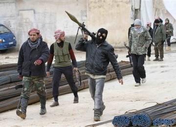 Pasukan pemberontak Suriah berjalan di sebuah kawasan di Idlib, Suriah, Kamis (9/2).