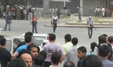 Pasukan pro pemerintah Suriah membawa senjata mereka mendekati kerumunan massa anti pemerintah di kawasan Kfar Suseh, Damaskus, Suriah, Senin (30/4) lalu.