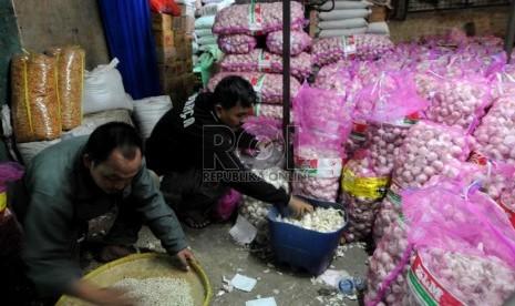 Pedagang memilah dan menimbang bawang putih di Pasar Induk Kramat Jati, Selasa (26/3).  (Republika/Wihdan Hidayat)