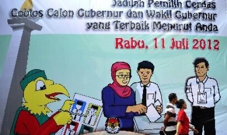 Pejalan kaki melintas di baliho sosialisasi Pilgub DKI yang dipasang di kawasan Cikini, Jakarta Pusat, Sabtu (12/5).