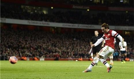 Pemain Arsenal, Santi Cazorla (kanan), melepaskan tembakan menjebol gawang Tottenham Hotspur dalam laga putaran ketiga Piala FA di Stadion Emirates, London, Sabtu (4/1).
