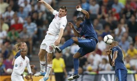 Pemain timnas Prancis, Florent Malouda (kanan) dan Patrice Evra, terlibat duel udara dengan gelandang Inggris, James Milner, di laga Grup D Piala Eropa 2012 di Donbass Arena, Donetsk, Ukraina, Senin (11/6).