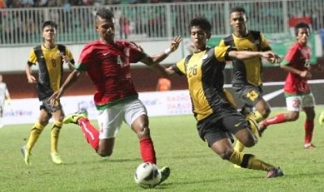 Pemain timnas Indonesia U-23, Syahrizal (dua kiri) berebut bola dengan pemain timnas U-21 Malaysia, Mohamad Irfan di Stadion Maguwoharjo, Sleman, Rabu (5/3).