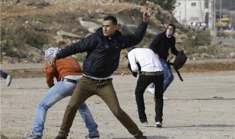 Pemuda Palestina tanpa rasa takut dan hanya menggunakan batu melakukan perlawanan terhadap tentara Israel di Jalur Gaza, Palestina, Sabtu (17/11).