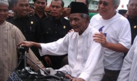 Pengasuh Ponpes Al Muttaqin, KH Muslim Rifai Imampuro atau Mbah Lim memboncengkan Iwan Fals pada rangkaian acara Tour Spiritual bersama dengan Al-Zastrouw dan Grup Musik Ki Ageng Ganjur beberapa waktu lalu.