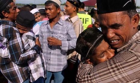 Pengungsi Rohingya saling berpelukan dan menangis usai melaksanakan salat Idul Fitri di penampungan sementara Desa Blang Ado, Kuta Makmur, Aceh Utara, Jumat (17/7).   (Antara/Rahmad)
