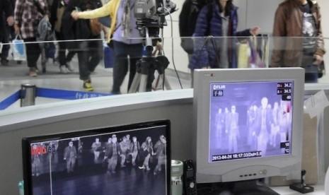 Penumpang melewati detektor temperatur tubuh di Bandara Internasional Taoyuan, Selatan Taiwan. Ini sebagai salah satu langkah untuk mendeteksi gejala flu burung