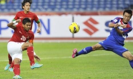Penyerang Indonesia, Bambang Pamungkas (kiri), menendang bola dibayangi bek Laos, Ketsada Souksavanh (kanan), pada pertandingan penyisihan Grup B Piala AFF 2012 di Stadion Bukit Jalil, Kuala Lumpur, Malaysia, Ahad (25/11) petang. Pertandingan tersebut bera
