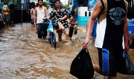 People walk through the flooded area in Jakarta. (illustration)