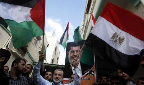 Perdana Menteri Palestina Ismail Haniyeh memegang bendera Palestina dan Mesir dengan latar belakang poster presiden Mesir terpilih Muhammad Mursi di Gaza, Palestina.