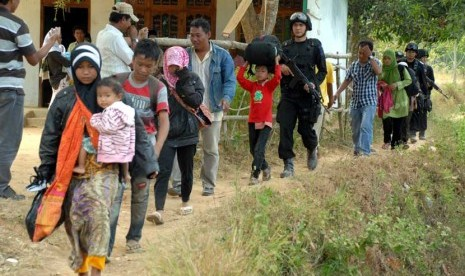 Personel Brimob mengawal sejumlah perempuan dan anak-anak, ketika berlangsungnya evakuasi dari tempat persembunyian mereka, di Desa Karanggayam dan Desa Bluuran, Sampang, Jatim, Senin (27/8). (Saiful Bahri/Antara)