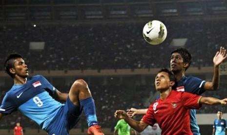 Pesepakbola Indonesia Hendra Adi Bayauw (tengah) berebut bola dengan pesepakbola Singapura Safirul bin Sulaiman (kiri) dalam pertandingan babak kualifikasi grup E Piala Asia (AFC) U-22 di Stadion Utama Riau, Pekanbaru, Riau, Ahad (15/7).
