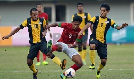 Pesepakbola Indonesia Yandi Sofyan berusaha melewati hadangan pemain Malaysia pada babak semifinal sepakbola Sea Games ke-27 di Naypyidaw, Myanmar, Kamis (19/2).
