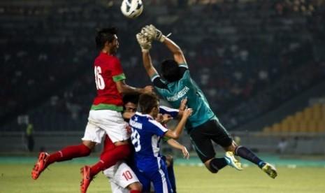 Pesepakbola timnas U-19 Indonesia, Hansamu Yama Pratama (kiri) dan penjaga gawang Laos, Bounpaseuth Niphavong (kanan), berjibaku berebut bola saat laga grup G kualifikasi Piala Asia (AFC) U-19 di Stadion Gelora Bung Karno, Senayan, Jakarta, Selasa (8/10) m
