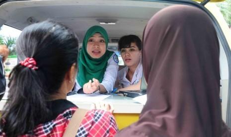 Petugas Badan Penyelenggara Jaminan Sosial (BPJS) menerangkan kepada warga cara mendapatkan kartu Jaminan Kesehatan Nasional (JKN) saat peluncuran JKN di RS Fatmawati, Jakarta, Rabu (1/1). Kartu JKN merupakan perlindungan kesehatan agar peserta memeroleh m