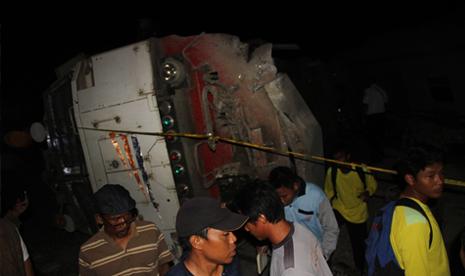 Petugas dan warga melihat lokomotif dari kereta api Eksekutif Bangunkarta jurusan Jakarta Surabaya yang terguling di Mundu, Cirebon, Jawa Barat, Sabtu (23/5) malam.