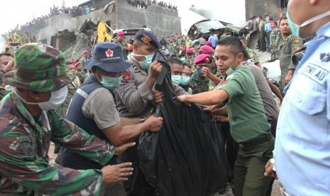 Petugas gabungan mengangkat kantong jenazah korban pesawat Hercules C-130 yang jatuh di Jalan Jamin Ginting, Medan, Sumatera Utara, Selasa (30/6). . (Antara/Irsan Mulyadi)