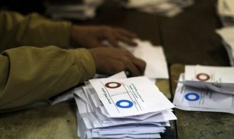 Petugas komite referendum sedang menyortir kertas suara berdasar pilihan 'ya' atau 'tidak' terhadap konstitusi baru Mesir.