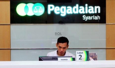 Petugas melayani nasabah di kantor Pegadaian Syariah, Jakarta, Senin (8/12).