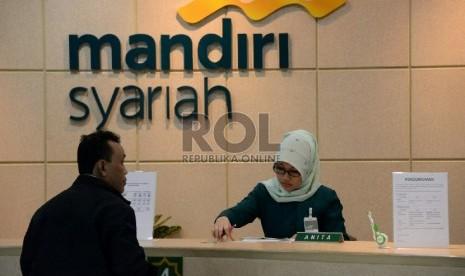 Petugas melayani nasabah di salah satu kantor cabang Bank Syariah Mandiri, Jakarta, Jumat (13/2).