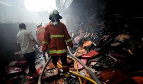 Petugas memadamkan api saat terjadi kebakaran