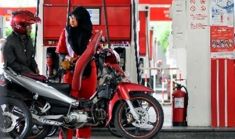 Petugas membantu warga mengisi bahan bakar minyak (BBM) di SPBU.
