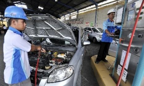 Petugas mengisi bahan bakar gas (BBG) ke sebuah mobil yang digunakan sebagai transportasi umum di Stasiun Pengisian BBG (SPBG) di Surabaya, Jawa Timur.