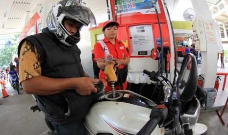 Petugas mengisi bahan bakar minyak sebuah sepeda motor di salah satu SPBU milik Pertamina di Jakarta.