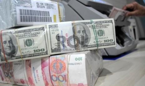 Petugas menunjukan mata uang dolar as di pooling cash bank mandiri