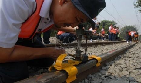 Petugas PT Kereta Api Indonesia (KAI) mengukur kerataan rel kereta api di kawasan Jatinegara,Jakarta,Kamis (6/9).   (Agung Fatma Putra)