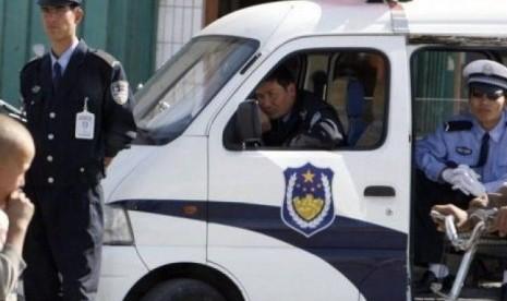 Polisi Cina saat melakukan razia terhadap rumah-rumah warga Muslim ...