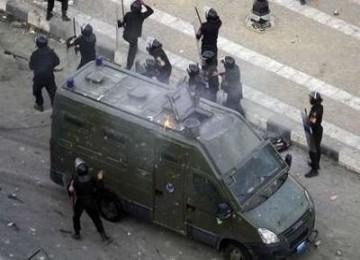 Polisi berlindung di dekat kendaraan lapis baja saat menghalau demonstran di Suez, Sabtu pagi waktu setempat.