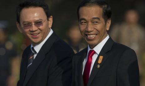 Presiden Joko Widodo (kanan) dan Gubernur DKI Jakarta Basuki Tjahaja Purnama (kiri) menyapa wartawan ketika berjalan menuju ke pesawat kepresidenan di Bandara Internasional Halim Perdanakusuma, Jakarta Timur, Selasa (28/7).