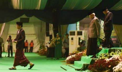 Presiden Joko Widodo (kiri) diikuti Ketua Pengurus Besar Nahdlatul Ulama (PBNU) Said Aqil Siradj (kanan) dan Pengurus PBNU Mustofa Bisri (kedua kanan) menuruni mimbar usai membuka Muktamar Nahdlatul Ulama ke-33 di Jombang, Jawa Timur, Sabtu (1/8).