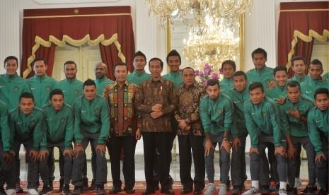 Presiden Joko Widodo (tengah) didampingi Menpora Imam Nahrawi (kelima kiri) serta Ketua PSSI Edy Rahmayadi (kelima kanan) berfoto bersama Tim Nasional Sepakbola Indonesia Piala AFF di Istana Merdeka, Jakarta, Senin (19/12).